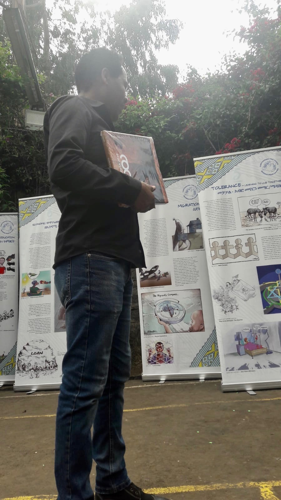 Le dessinateur de presse Elias Areda devant l'exposition pédagogique Cartooning for Peace