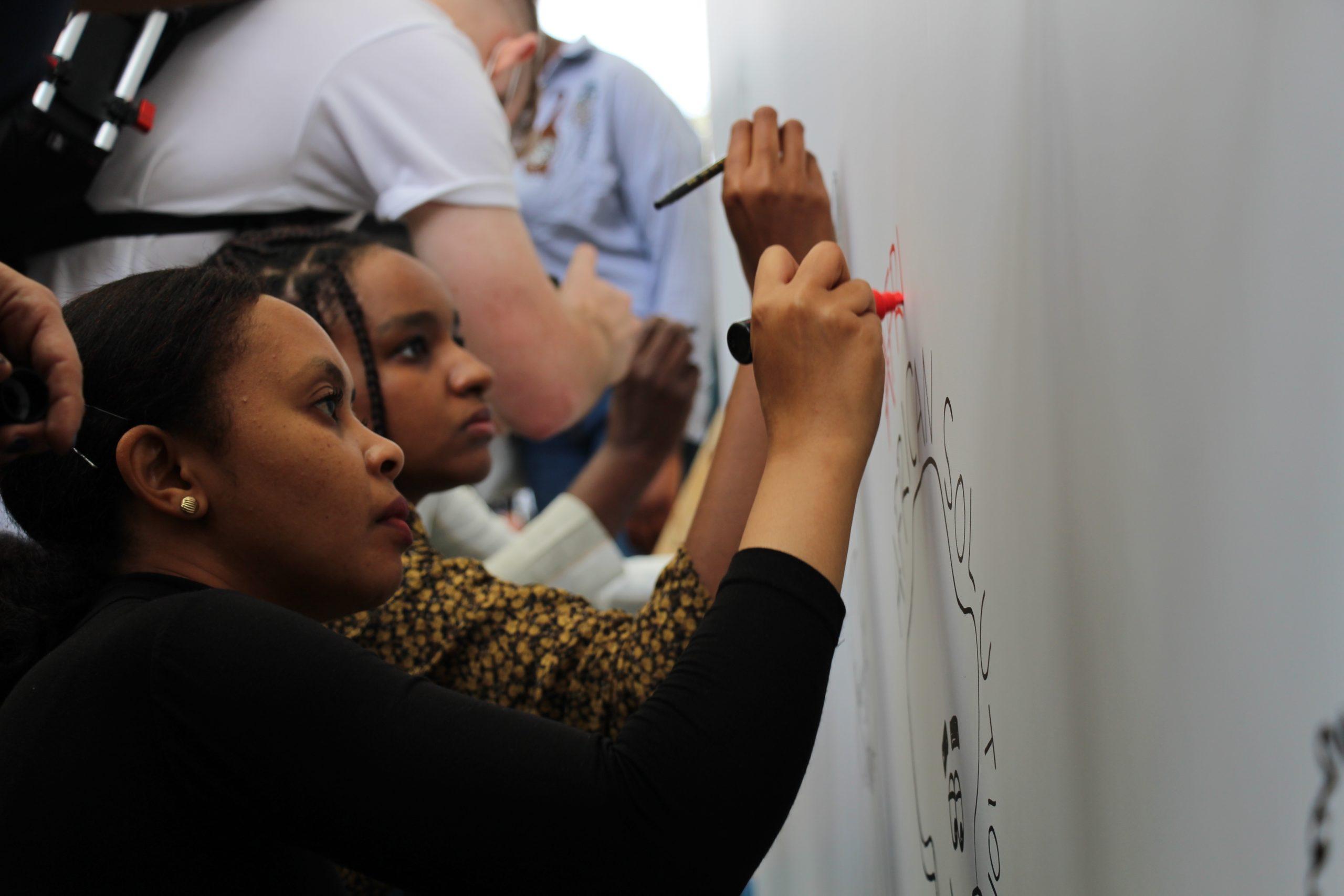 Yemi (Ethiopie) et Alaa Satir (Soudan) en train de dessiner pour la fresque en direct